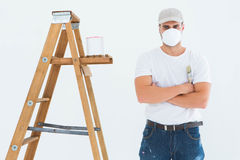 Man with paintbrush standing arms crossed by ladder Stock Images