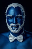 Man painted in blue color with snowy hair and beard. On black background royalty free stock photo