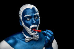 Man painted in blue color with snowy hair and beard eating chili pepper Stock Images