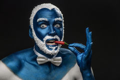 Man painted in blue color with snowy hair and beard eating chili pepper Royalty Free Stock Images
