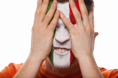 Man with painted face covers face with hands. Stock Images