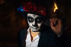 A man with a painted face of a skeleton, a dead zombie, in the city during the day. day of all souls, day of the dead, halloween, stock photo