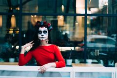 A man with a painted face of a skeleton, a dead zombie, in the city during the day. day of all souls, day of the dead, halloween, royalty free stock photography