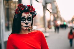 A man with a painted face of a skeleton, a dead zombie, in the city during the day. day of all souls, day of the dead, halloween, royalty free stock image