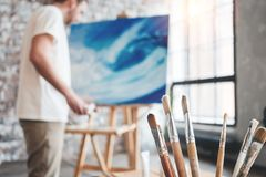 Man painter stand near big window in workshop with canvas on easel. Brushes close up on wooden table in studio. Flare effect. Arti. St in loft space. Blurred Royalty Free Stock Photography