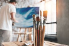 Man painter working in workshop in back of the canvas and drawing. Brushes close up on wooden table in studio. Flare effect. Artist in loft classe stock photo