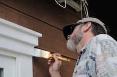 Man Painting. A senior man painting the doorway with white paint Royalty Free Stock Photos