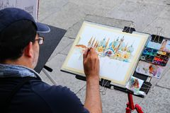 Man painting Basilica of Saint Mark at Piazza San Marco in Venice, Italy. Venice is one of the most important tourist destinations in the world for its stock photo