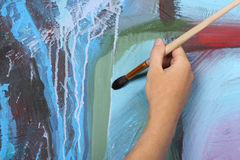 Man painting blue abstract picture Stock Images