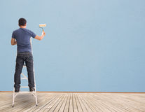 Man Painting On Blue  Blank Wall. Asian MAn With Paintbrush And Blue Blank Wall Stock Image