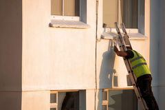 A man painting a building Stock Image