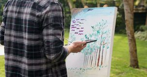 Man painting on canvas in the garden 4k. Mature man painting on canvas in the garden 4k stock video footage