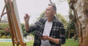Man painting on canvas in the garden 4k. Mature man painting on canvas in the garden 4k stock footage