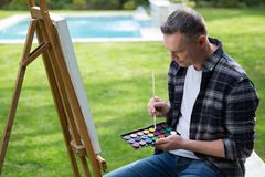 Man painting on canvas in garden. On a sunny day royalty free stock photo