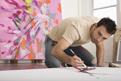 Man Painting On Canvas In Studio. Young man painting on canvas on studio floor stock photography