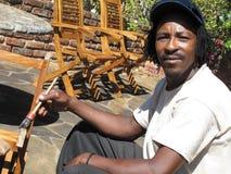 Man painting chair outdoors Stock Photos