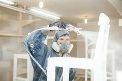 Man painting chair into white paint in respiratory mask. Application of flame retardant ensuring fire protection. Airless spraying device Stock Photos