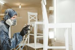 Man painting chair into white paint in respiratory mask. Application of flame retardant ensuring fire protection. Airless spraying device Royalty Free Stock Image