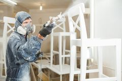 Man painting chair into white paint in respiratory mask. Application of flame retardant ensuring fire protection. Airless spraying device Royalty Free Stock Photo