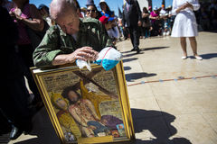 Man with a painting of Christ praying at the Sanctuary of Fatima during the celebrations of the apparition of the Virgin Mary in F. Fatima, Portugal - May 13 Stock Photo