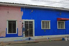 Man painting a colorful house in the streets of the colonial city of Leon, Nicaragua. Central America Royalty Free Stock Image