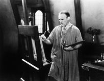 Man painting on an easel with a paintbrush Royalty Free Stock Photo