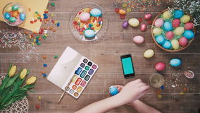 Man painting easter egg and smart phone with green screen lies on table decorated with easter eggs. Top view. Stock footage of Man painting easter egg and smart stock video