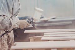 Man painting furniture details. Worker using spray gun. Stock Photography