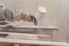 Man painting furniture details. Worker using spray gun. Royalty Free Stock Photo