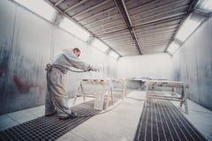 Man painting furniture details. Worker using spray gun. Royalty Free Stock Image