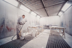 Man painting furniture details. Worker using spray gun. Royalty Free Stock Photography