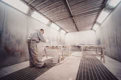 Man painting furniture details. Worker using spray gun. Stock Photo