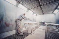 Man painting furniture details. Worker using spray gun. Stock Image