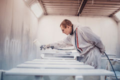 Man painting furniture details. Worker using spray gun. Stock Photos