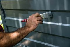 Painting the garage door. A man is painting the garage door Stock Photos