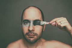 Man painting his face with a pencil and turning it black and white. Concept: portrait of a man painting his face with a pencil and turning it black and white Stock Image