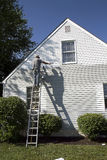 Man Painting Home. Man (Senior) painting house late afternoon with his full body shadow casted on house Royalty Free Stock Image