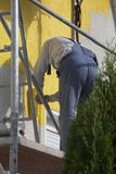 Man painting house. Man on scaffold painting house with roller Stock Photos