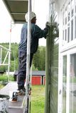 Man painting house. Man standing on a scaffold painting a house green Royalty Free Stock Photography