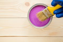 Man painting a house. Man's hand in blue glove. A tin can of fuschsia oil paint with a brush on a light uncolored wooden background. Close up. Top view. Space Royalty Free Stock Image