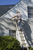 Man Painting House (Senior). Older gentleman painting his house during his retirement - late afternoon with his body shadow casted on house Royalty Free Stock Photography