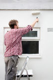 Man painting house wall. DIY Home Improvement. Stock Images