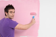 Man painting nursery wall. Young man painting nursery wall pink Stock Photography