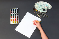 Man painting on a piece of pencil on a white sheet. On a gray background Stock Image