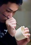 Man painting pottery. A Japanese man painting a design onto Satsuma ware pottery stock photo