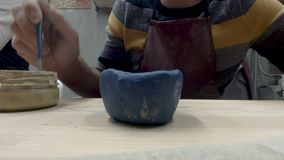 Man painting pottery stock video