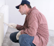 Man painting radiator Royalty Free Stock Photos