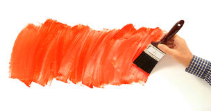 Man painting red paint on white wall, holding paint brush Stock Image