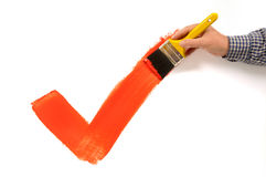 Man painting red checkmark or tick, holding paintbrush, white background Royalty Free Stock Photography