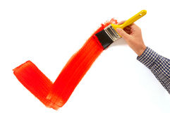 Man painting red tick or checkmark, holding paintbrush Royalty Free Stock Images